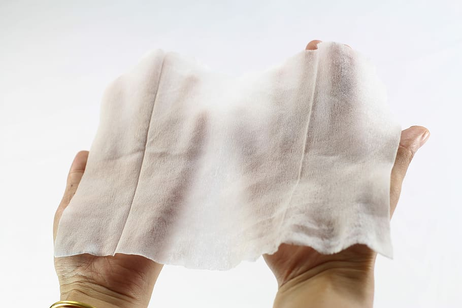 hands holding a screen wipe napkin