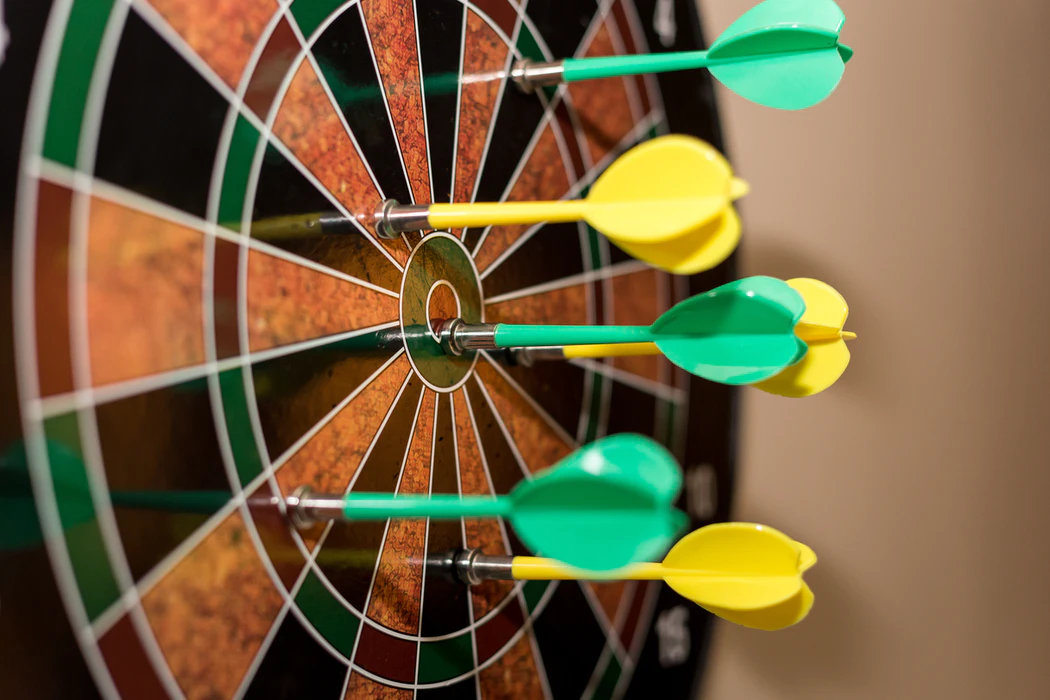 A dart board with darts around the bull's eye